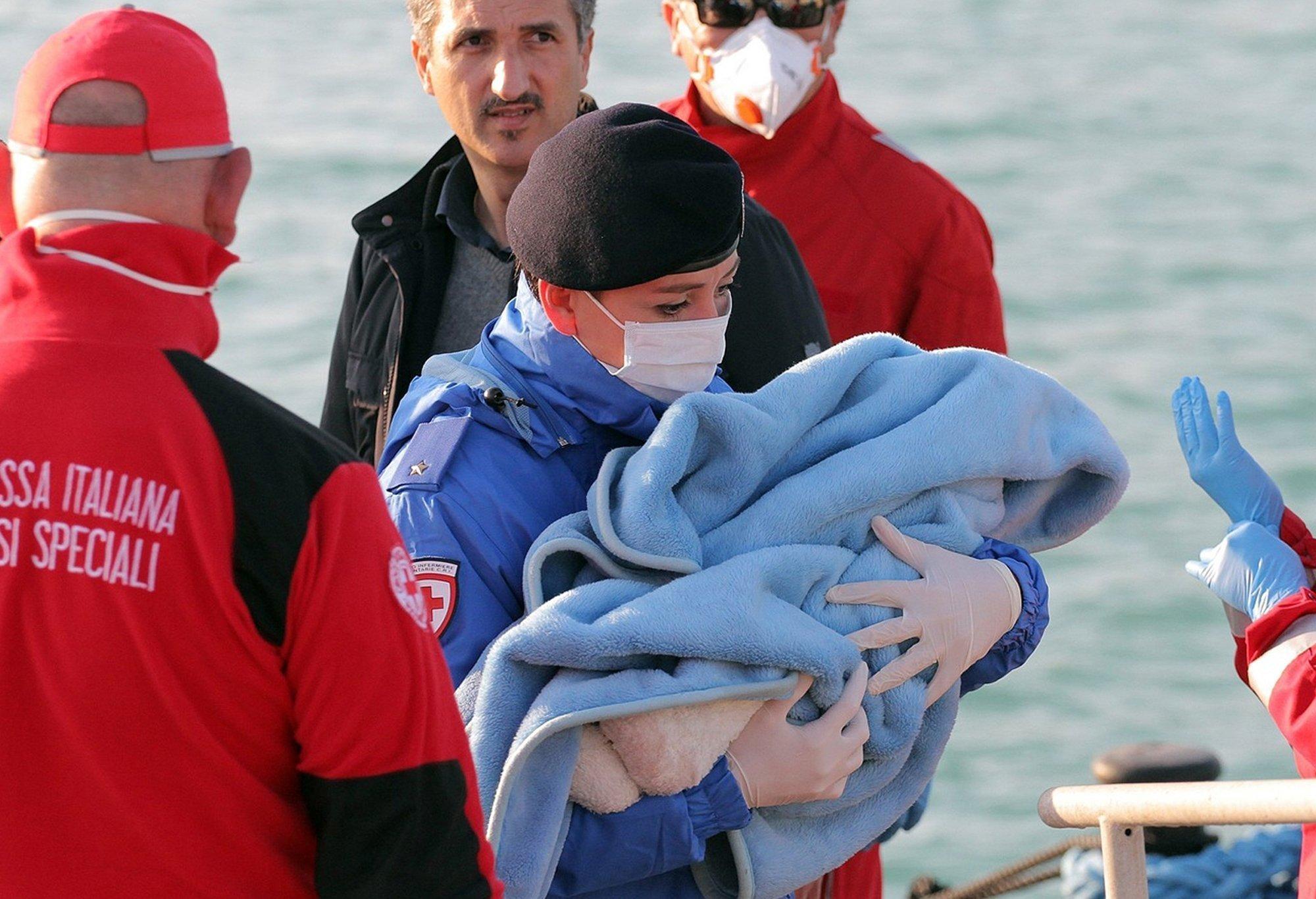 Волонтер Красного креста со спасенным ребенком во время спасательной операции береговой охраны Италии у острова Сицилия.