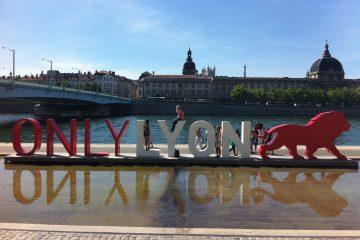 Визуально-текстовый объект «ONLY LYON» на набережной на фоне дворца.