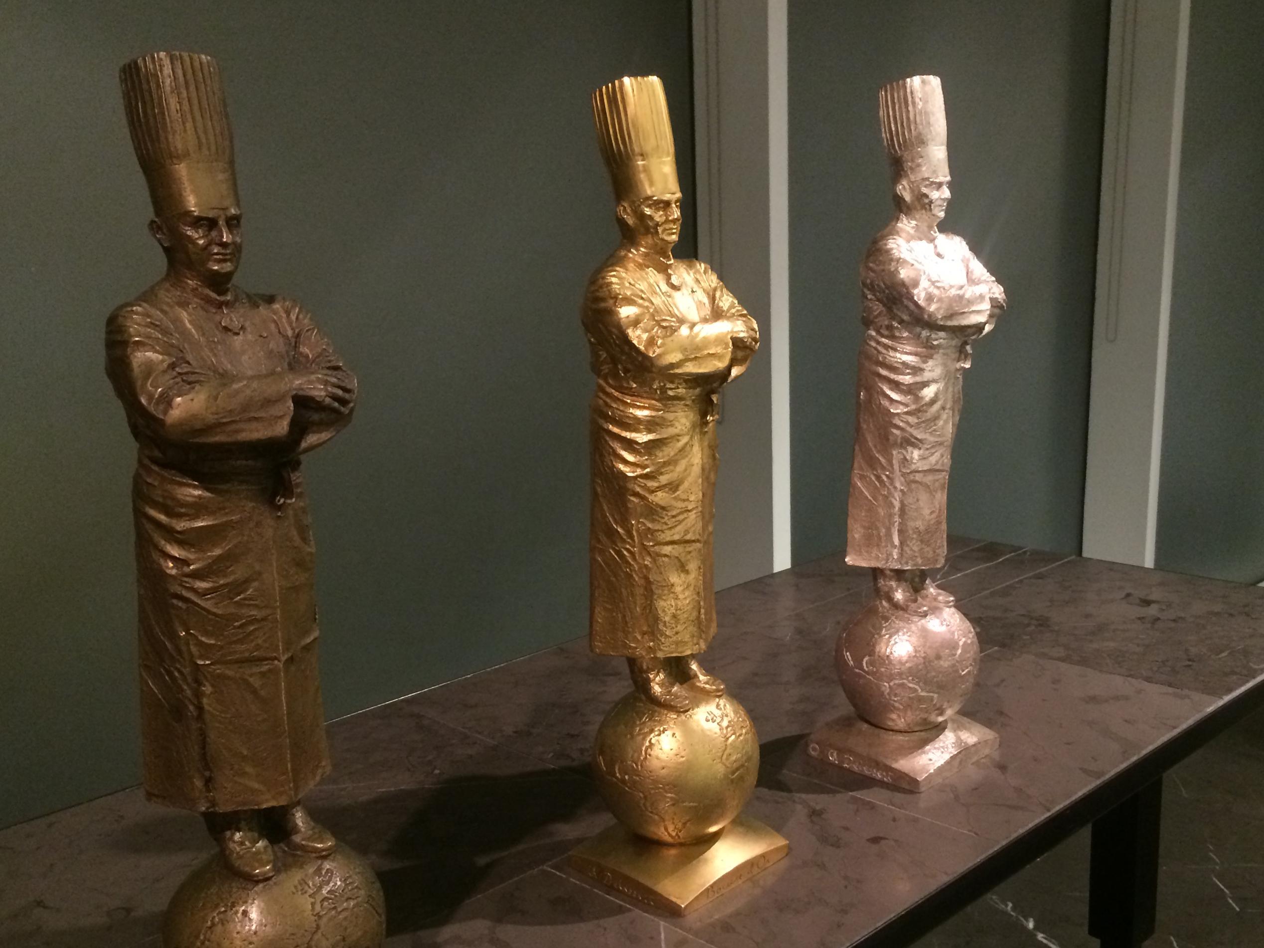 Золотая, серебряная и бронзовая статуэтки шефа Поля Бокюза. Источник http://onfoodietrail.com/