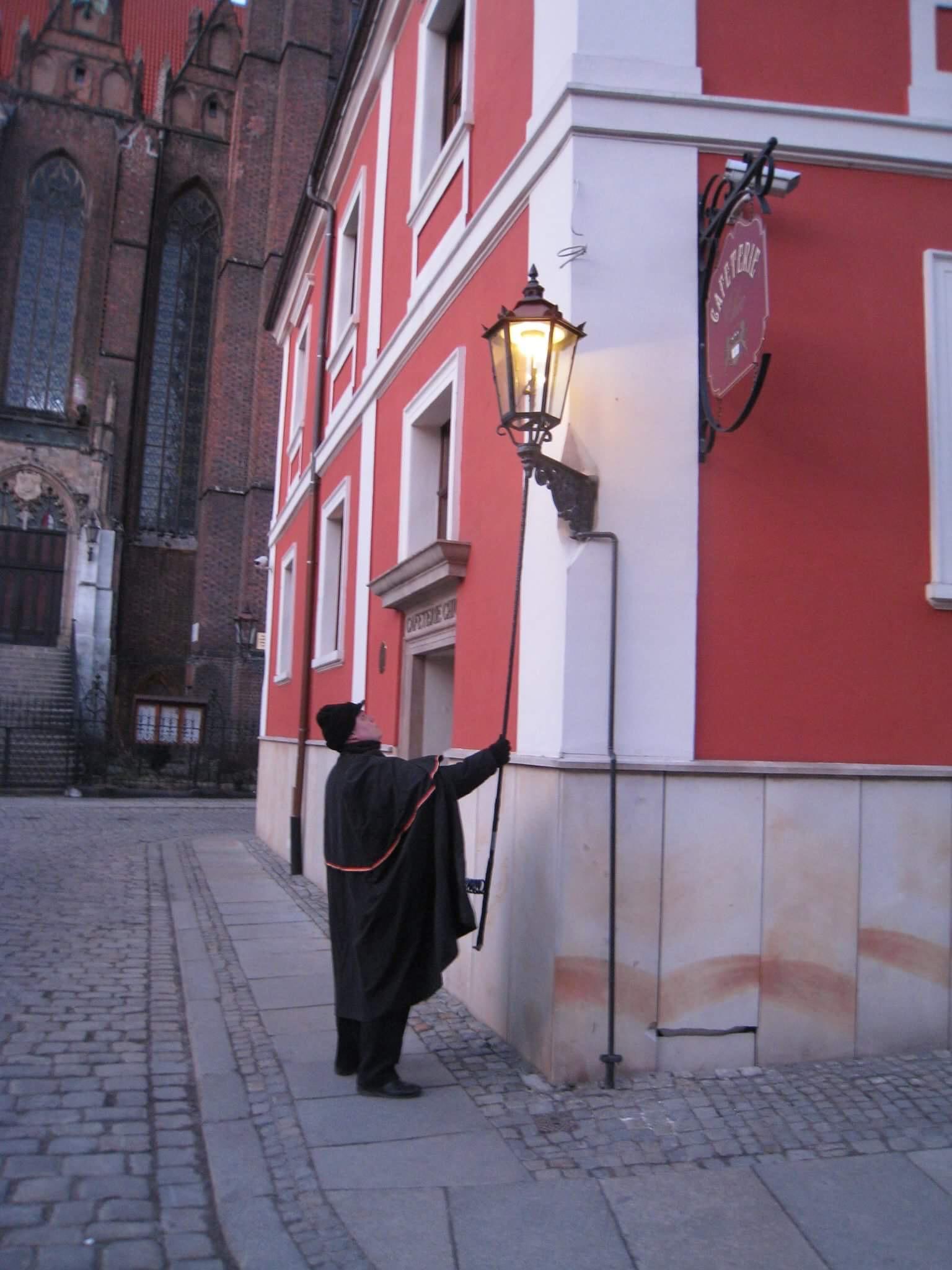 Фонарщик зажег газовый фонарь. Огонь разгорелся. Вроцлав. Польша.