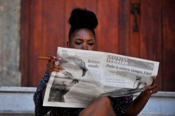 Кубинская женщина читает свежую газету с печальными новостями.