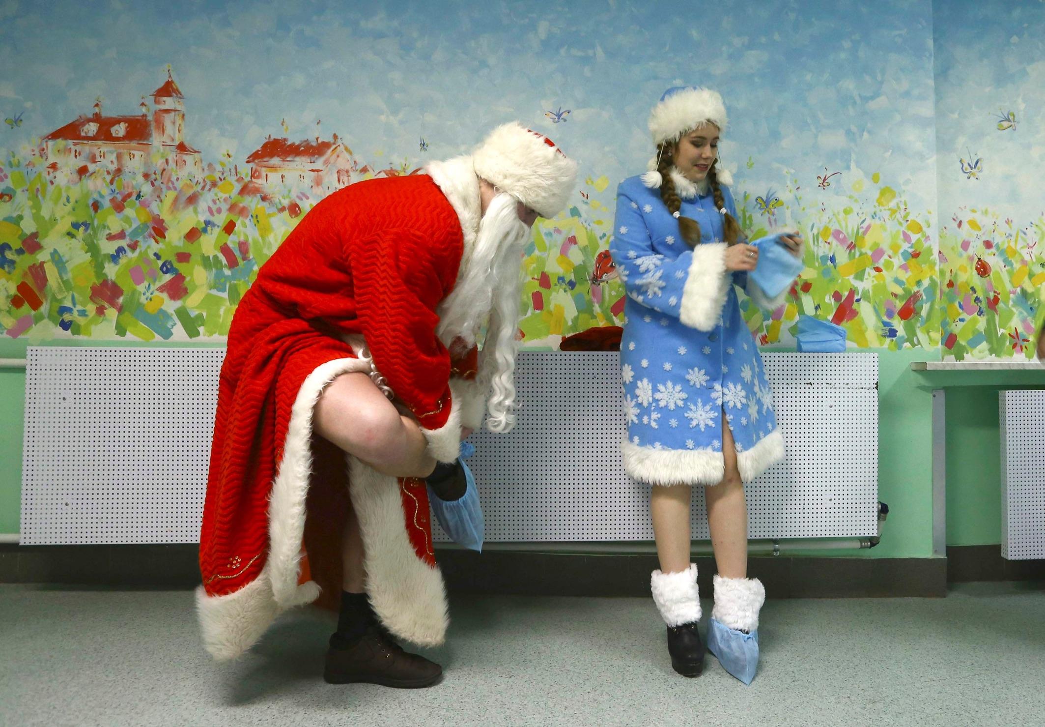 Дед Мороз и Снегурочка обуваются в бахилы для посещения детей в Научно-практическом центре педиатрии в Минске. Автор фото: Василий Федосенко/Reuters. Источник: http://avax.news